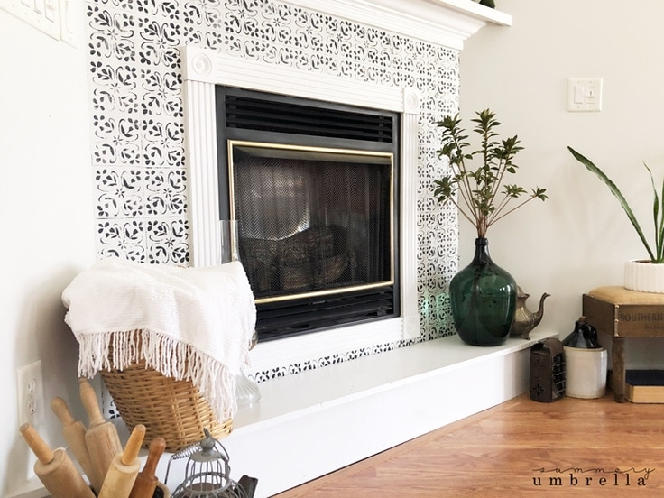 A white fireplace with DIY faux tiles painted on with a stencil.