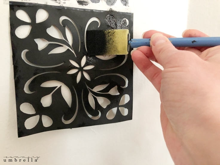 Using black paint to paint a tile stencil on a beige fireplace.