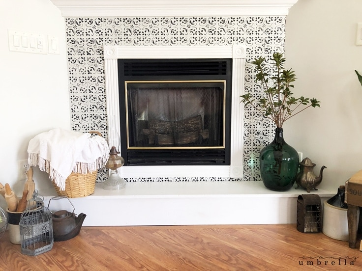 A white fireplace with black DIY faux tiles painted on it.