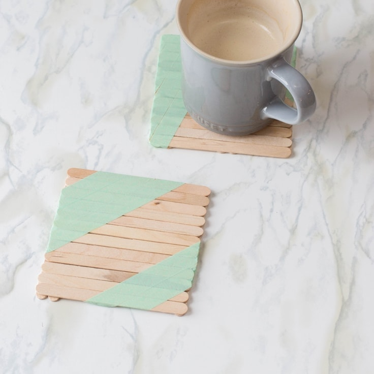 DIY drink coasters made out of popsicle sticks. A grey coffee mug sits on one of them.