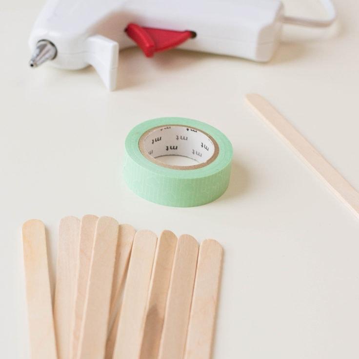 A close up of popsicle sticks, green washi tape and a glue gun.