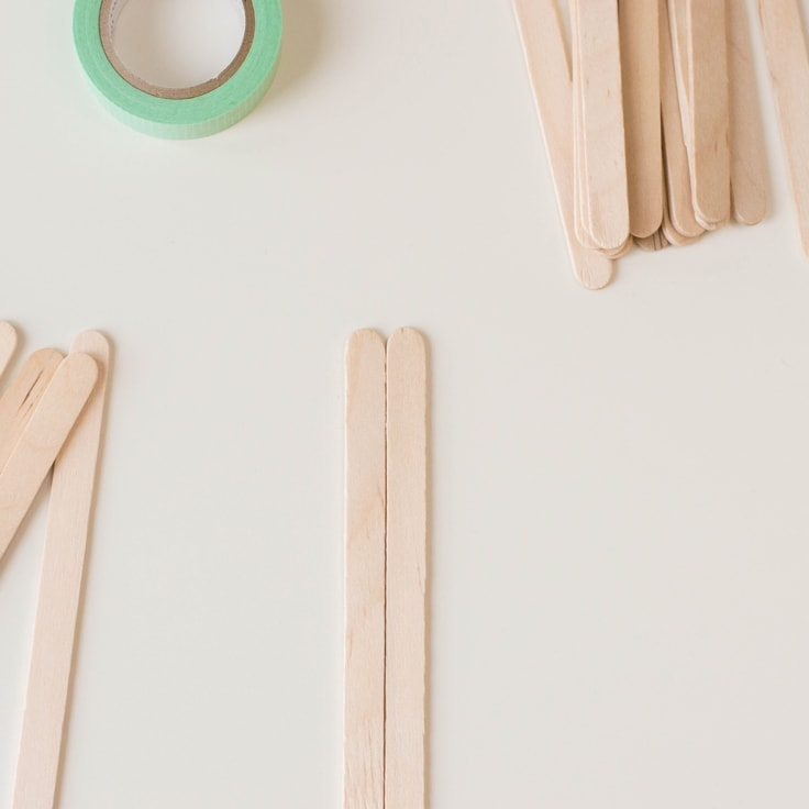 How to make a popsicle stick craft - first line up two sticks side by side.