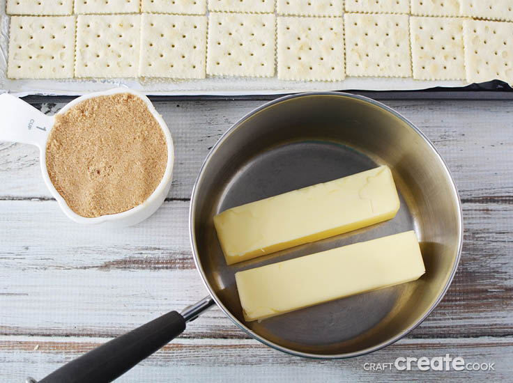 2 sticks of butter in a saucepan with brown sugar and saltine crackers in the background