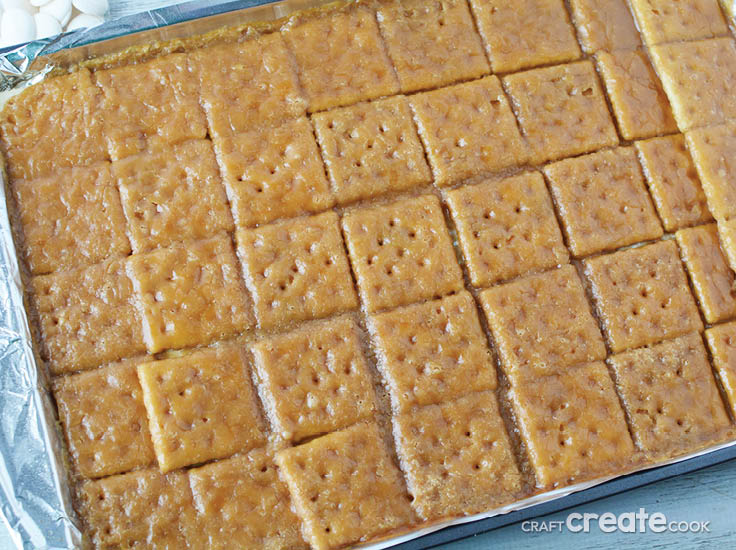 toffee and saltine crackers on a baking sheet after baking in an oven