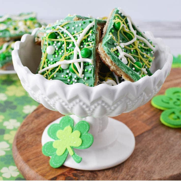 green and white saltine cracker toffee St. Patrick's Day snack in a white bowl