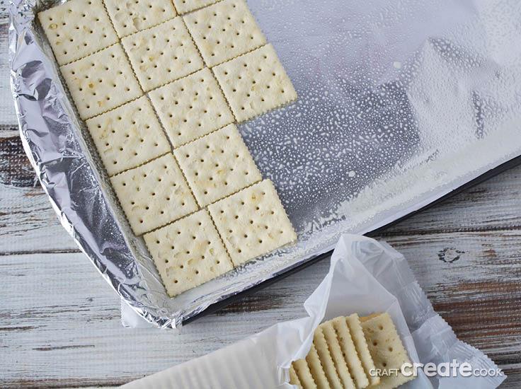 saltine crackers on an aluminum foil lined baking sheet