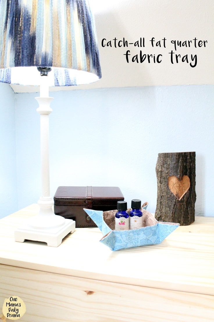 A hand-sewn fat quarter fabric tray sitting on a nightstand with essential oils bottles inside.