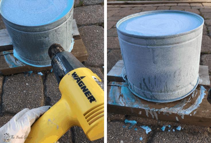 Using a heat gun to age a galvanized metal pail.