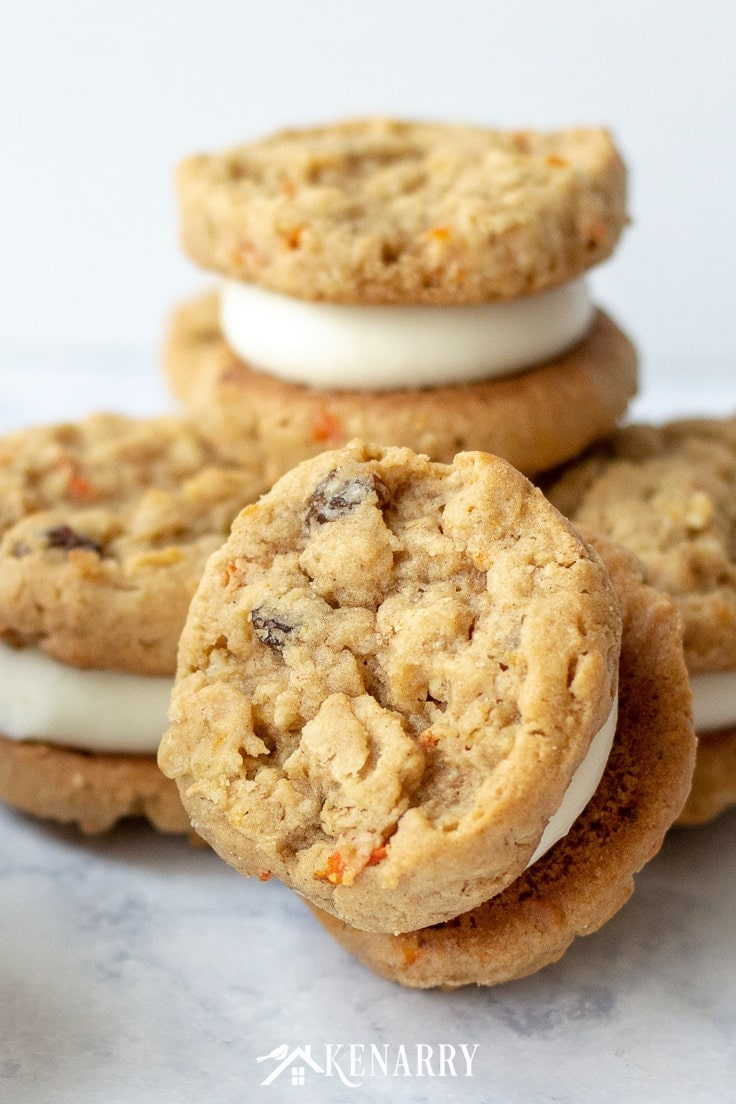 A large carrot cookie is front facing so you can see the raisins, minced carrots and hearty old fashioned oats. In the center of the cookie sandwich there is a layer of cream cheese to make this like a bite-sized carrot cake. In the background there are several other cookies in small stacks.