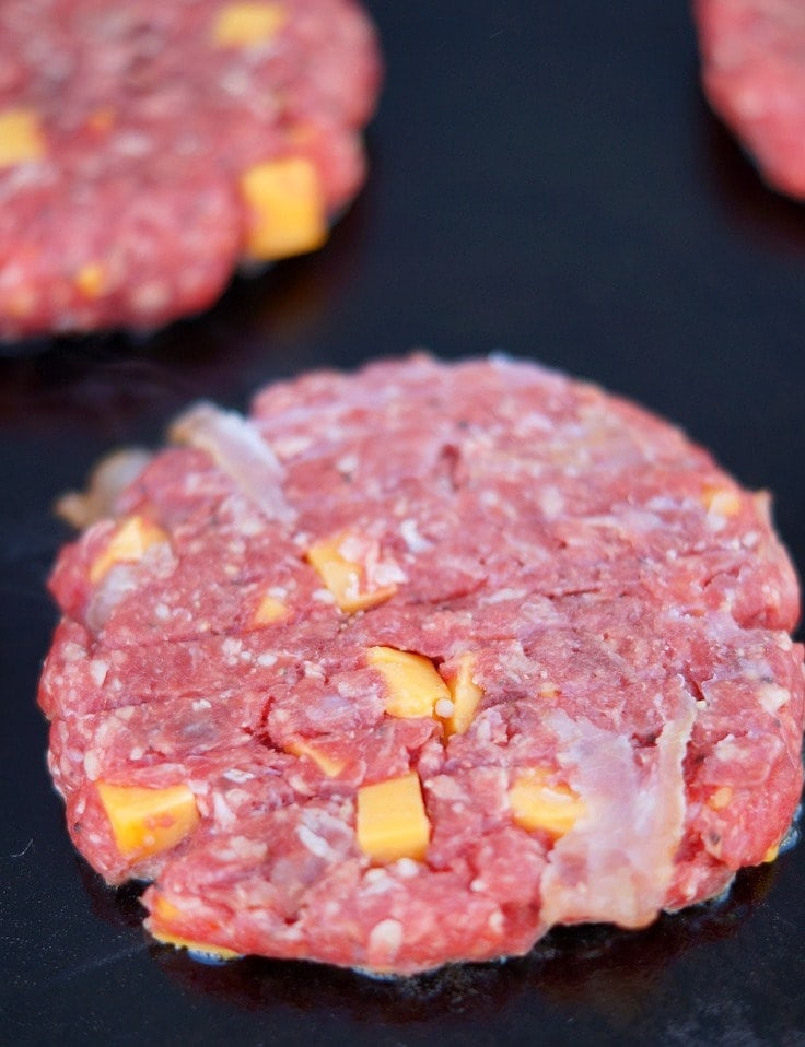 A raw hamburger patty stuffed with bacon and cheddar cheese