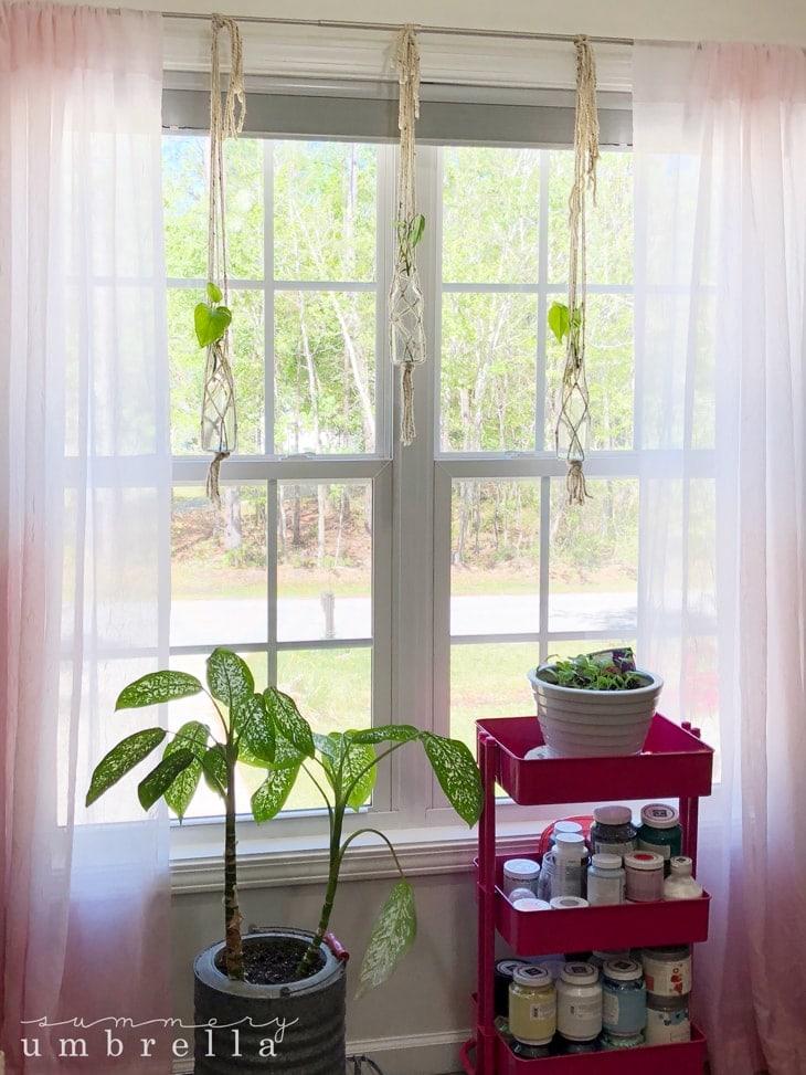 3 wool macrame hanging planters in the window.