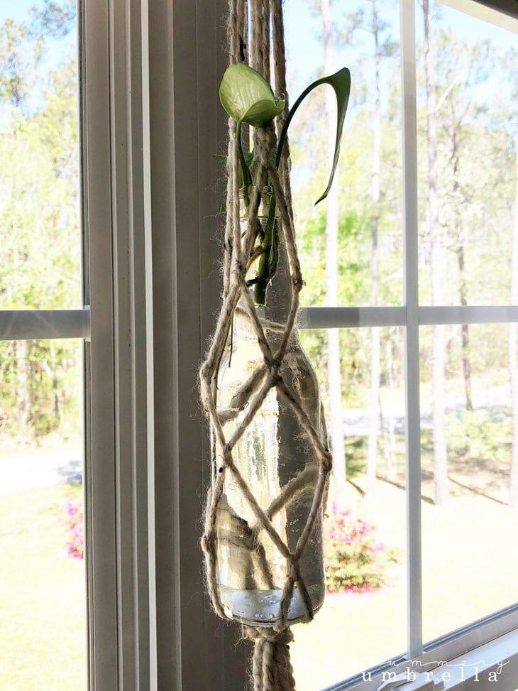 A glass bottle hanging in a wool yarn macrame hanger