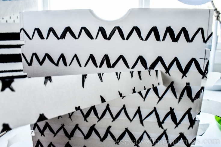 Peeling the tape off a white wood crate. The tape was used as a stencil for the black chevron pattern.