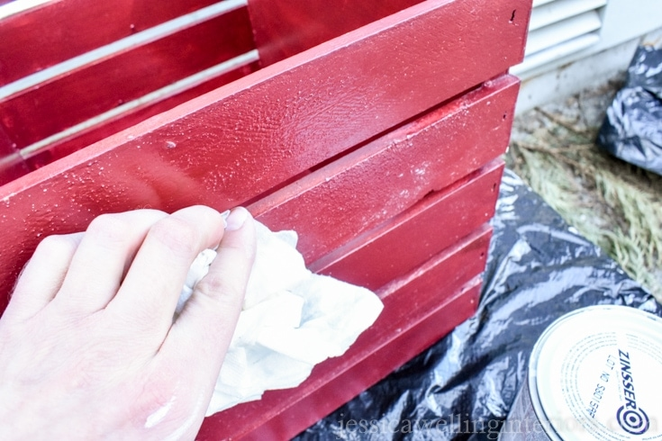 Wiping down a red crate with a damp cloth.