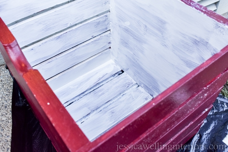 A red crate with white primer paint on the inside.