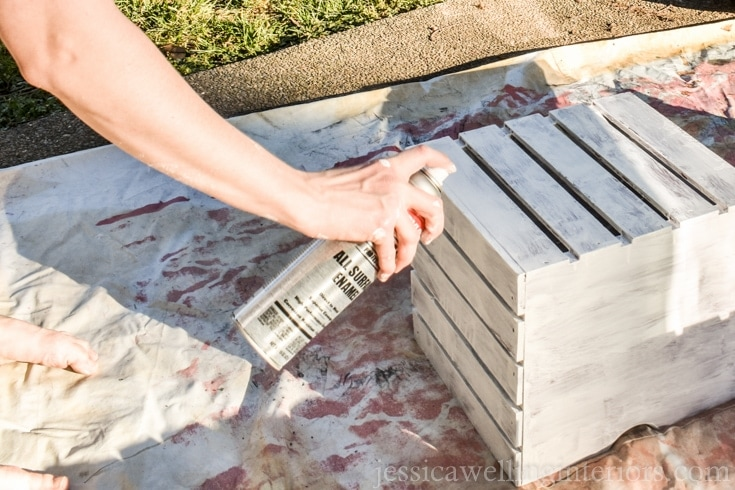 Spray painting a wood crate on a drop cloth.