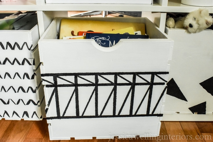 A white storage crate with hand-painted black block line art.