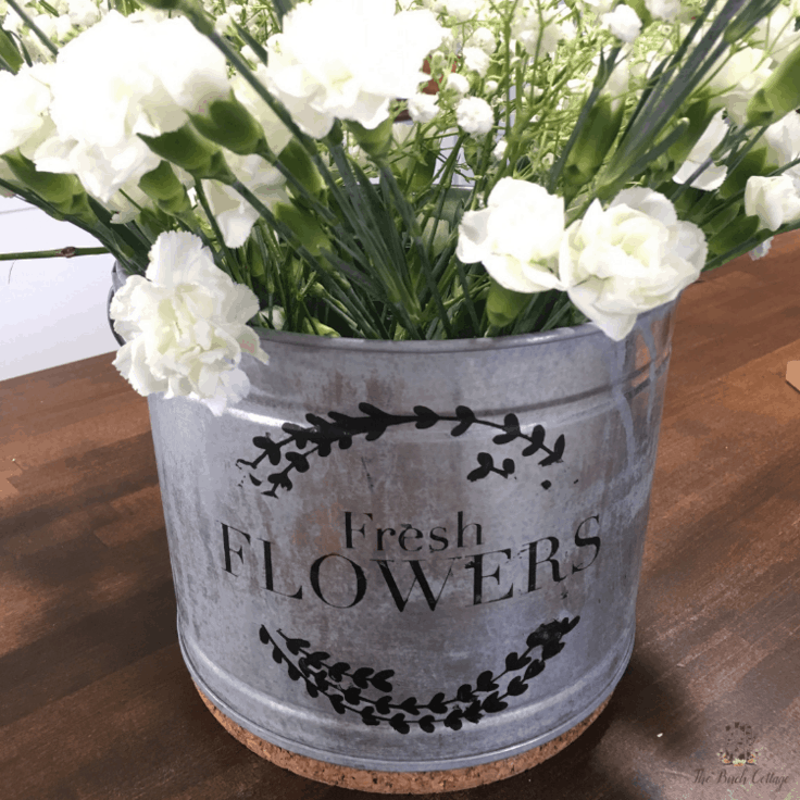 """A galvanized metal pail with the words """"fresh flowers"""" stenciled on the front."""""""