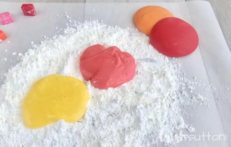 Melted Starburst on a layer of two powders ready to mix and create edible slime.