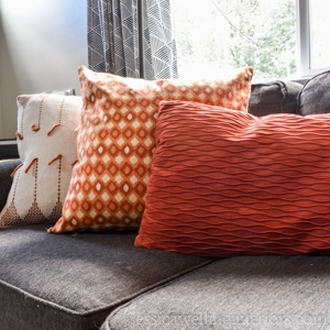 image of sofa with three pillows with easy throw pillow covers in orange