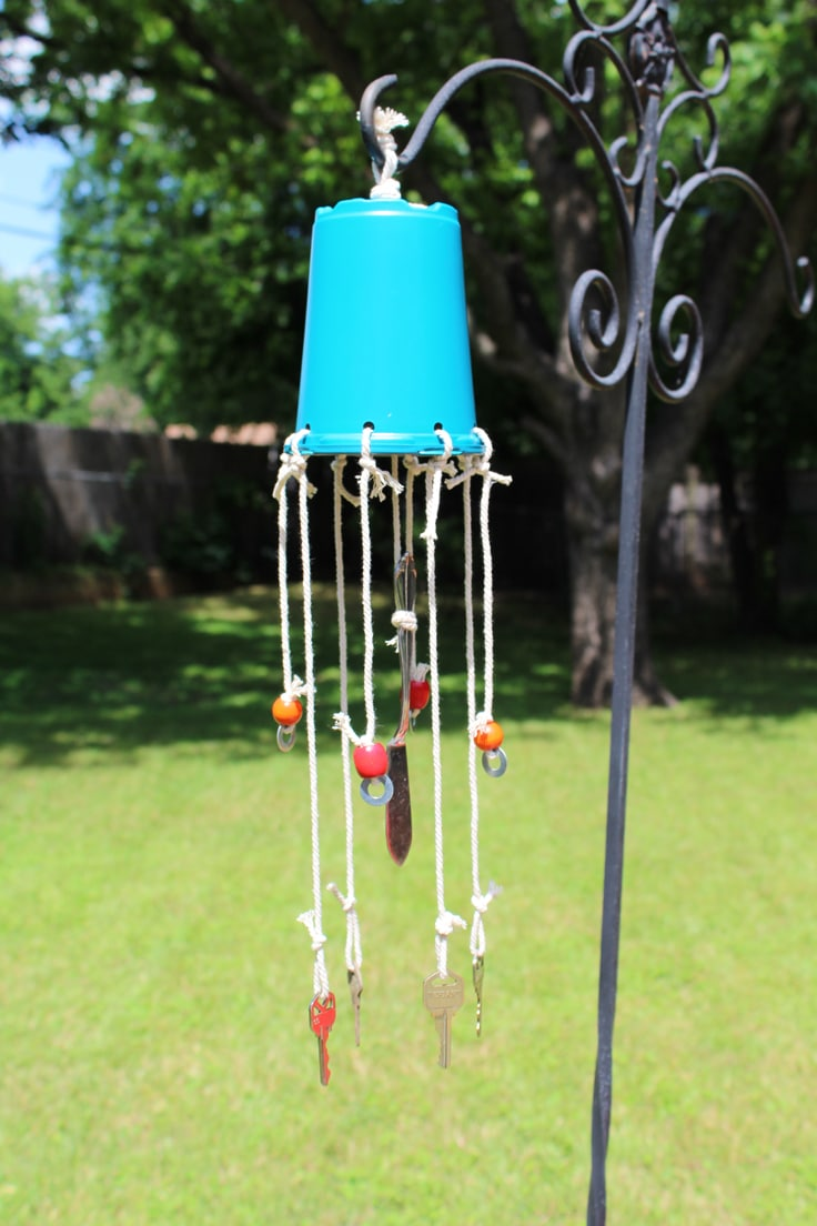 A blue wind chime with keys hanging from a hook