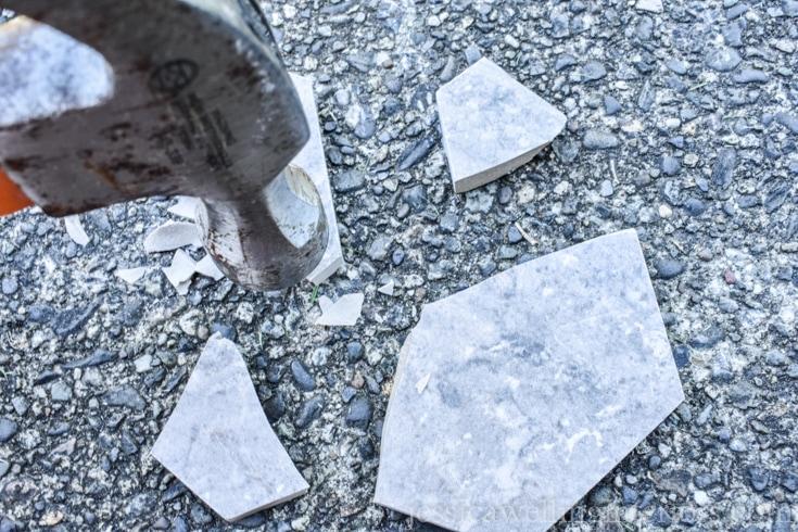 A hammer breaking hexagon tile to make kintsugi coasters