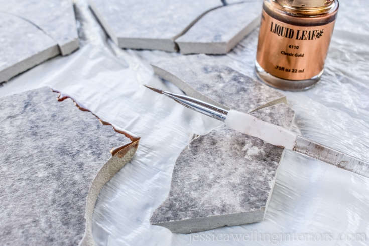 image of broken edges of hexagon tiles being painted with gold leaf to make kintsugi tile coasters