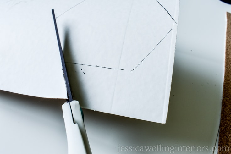 image of scissors being used to cut out a hexagon shape of self-adhesive cork sheet to create a backing for the kintsugi tile coaster