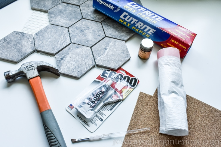 image of supplies needed to make diy kintsugi coasters: hexagon tiles, hammer, gold leaf paint, waxed paper, E6000 adhesive, small paint brush, and plastic garbage bags
