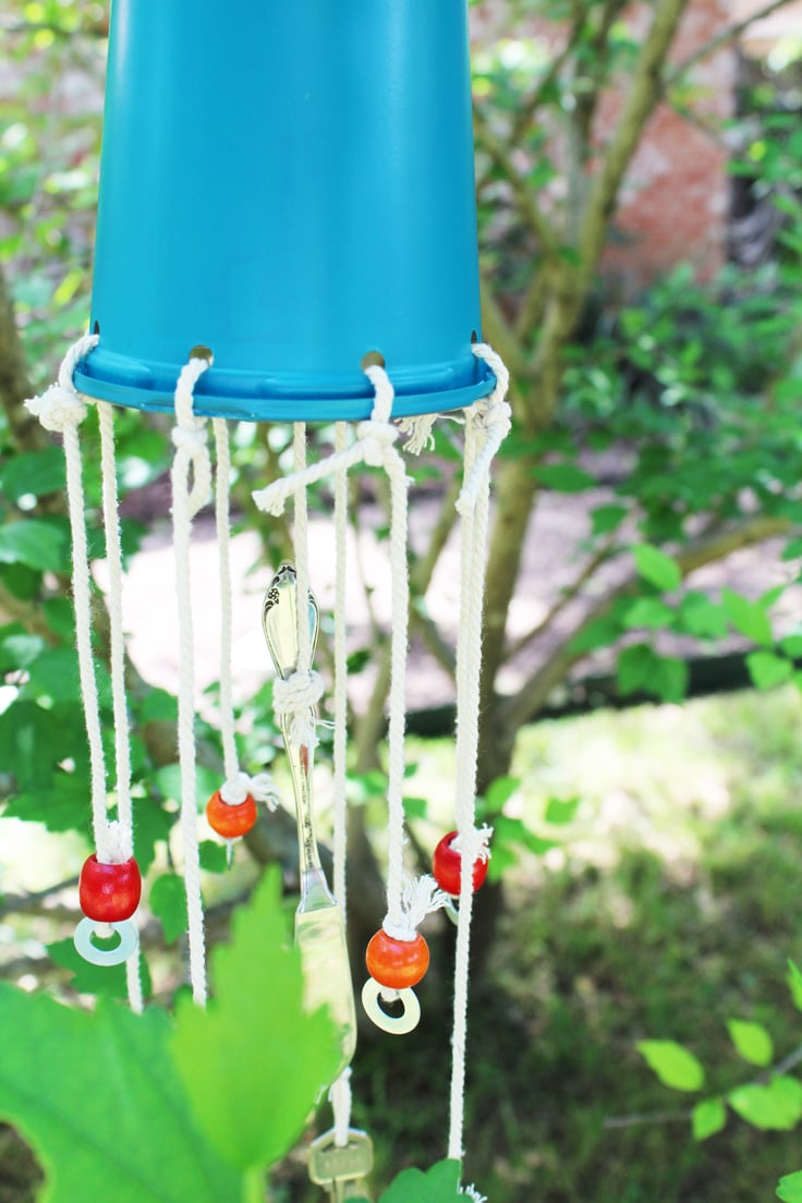 Close up of a blue wind chime hanging in a green tree