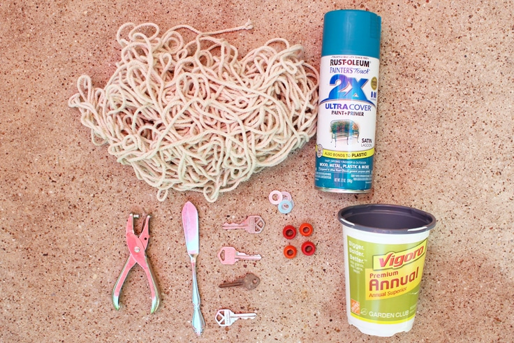 Wind chime supplies including cord, spray paint, a hole punch, a pot, and small found items.