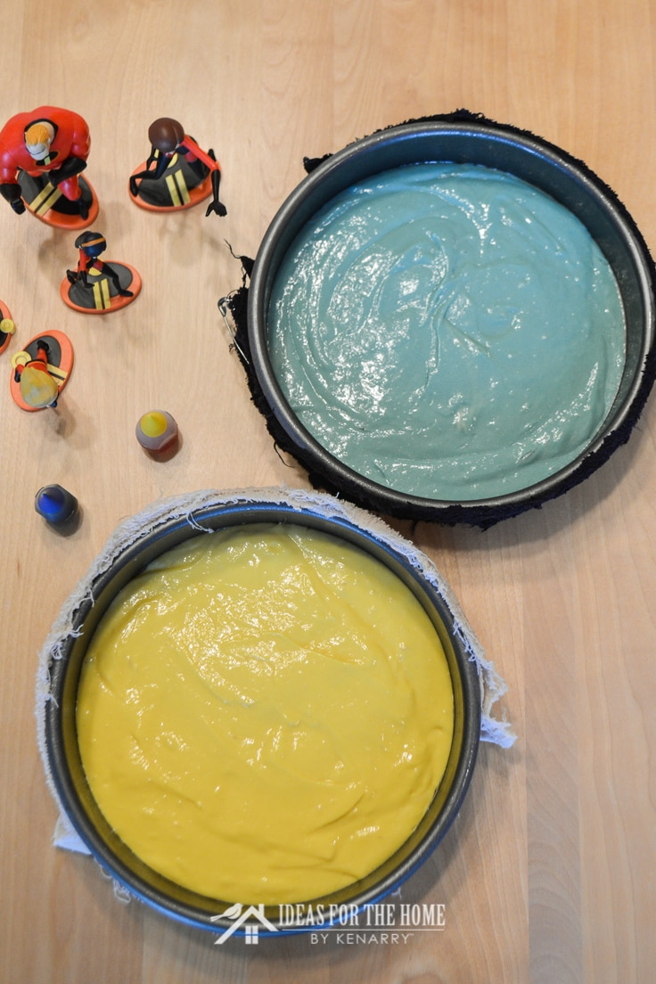 Overhead shot of Incredibles figurines, food coloring bottles and two round cake pans. One has yellow cake batter and the other has blue cake batter.