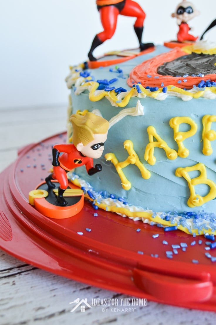 A toy action figure of Dash from The Incredibles appears to be running around the side of a round double layer birthday cake