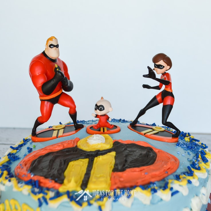 A toy action figures of Mr. Incredible, Jack Jack and Elastigirl from The Incredibles on top of a round double layer cake - an easy Incredibles birthday cake idea