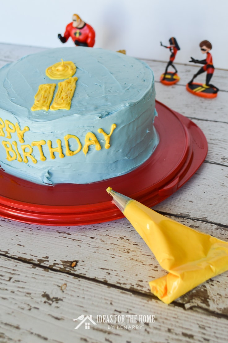 """Cake decorating bag filled with yellow frosting being used to write """"Happy Birthday"""" on the side of a double layered round cake covered with blue frosting."""