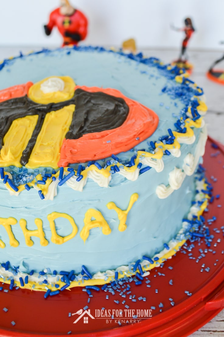 Close up of the edge of an Incredibles birthday cake trimmed with frosting and covered with various types of blue candy sprinkles.
