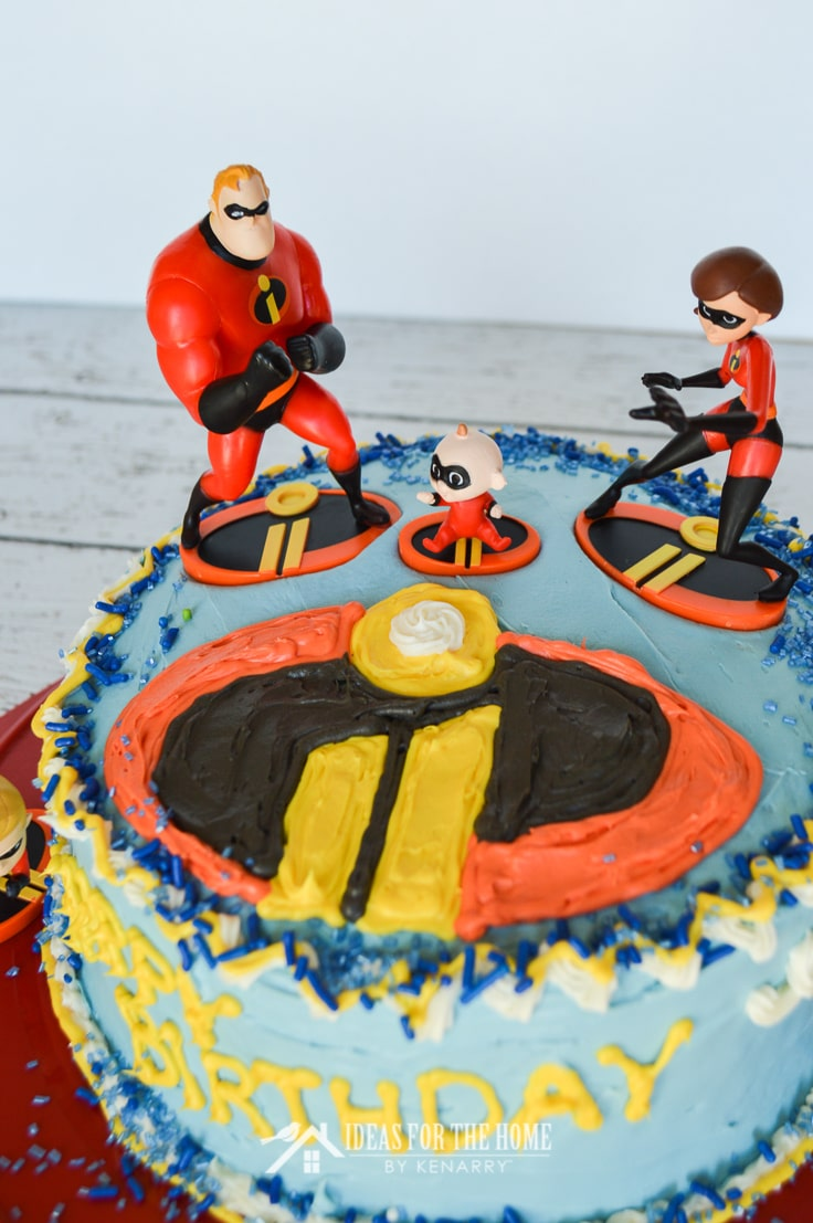 An easy Incredibles birthday cake idea showing a close-up of toy action figures on top of a round double layer cake