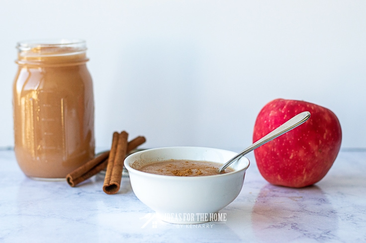 Bowl of applesauce with cinnamon sticks, a jar of applesauce and a fresh apple