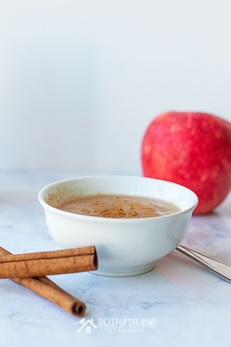 Bowl of applesauce with cinnamon sticks and a fresh apple