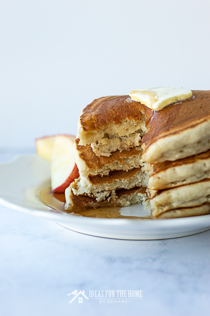 A wedge sized bite taken out of the side of stack of cinnamon pancakes with maple syrup and butter