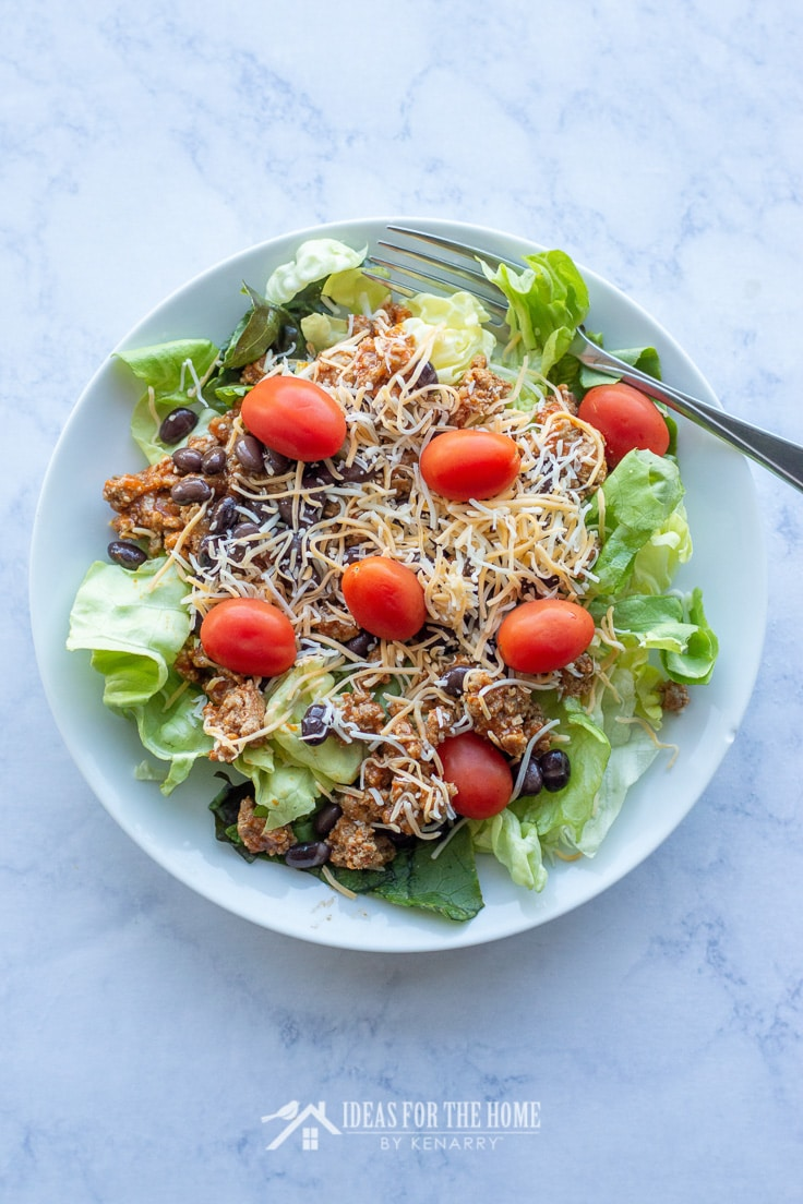 Lettuce topped with ground beef, crushed tortilla chips, black beans, tomatoes, and cheese to make a crowd pleasing taco salad for any summer picnic or potluck