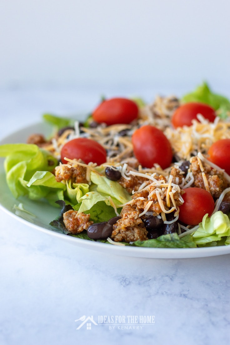 A close up of the ingredients in a summer salad made of taco meat, crushed chips, cheese, tomato and black beans with a tangy dressing