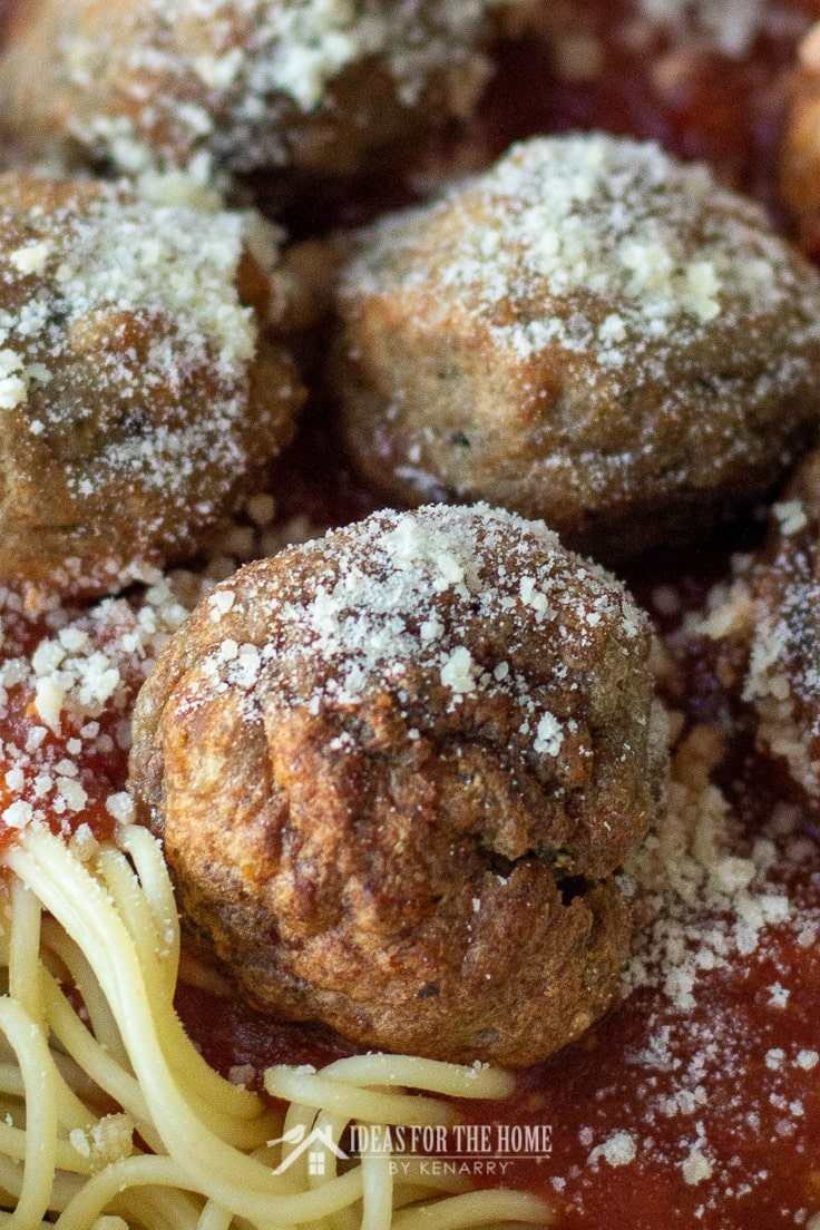 Close up of a homemade italian meatball on top of spaghetti noodles