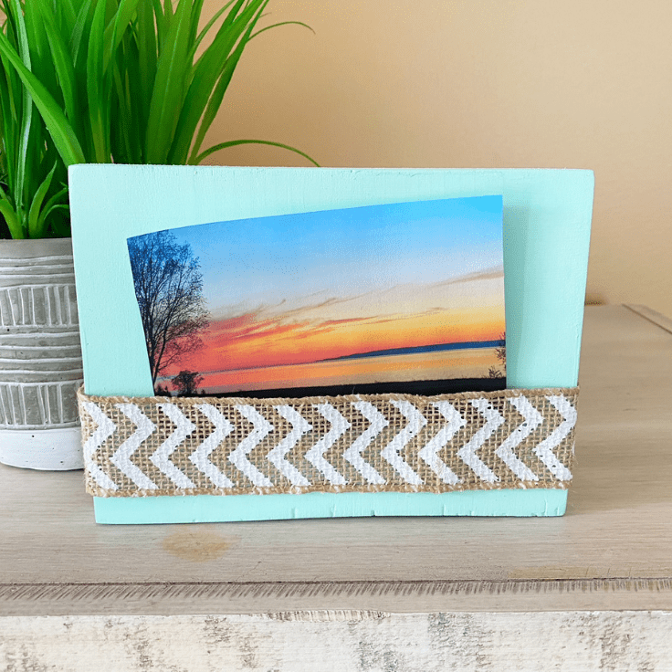 Wood block and burlap ribbon photo frame displaying a picture of a sunset.