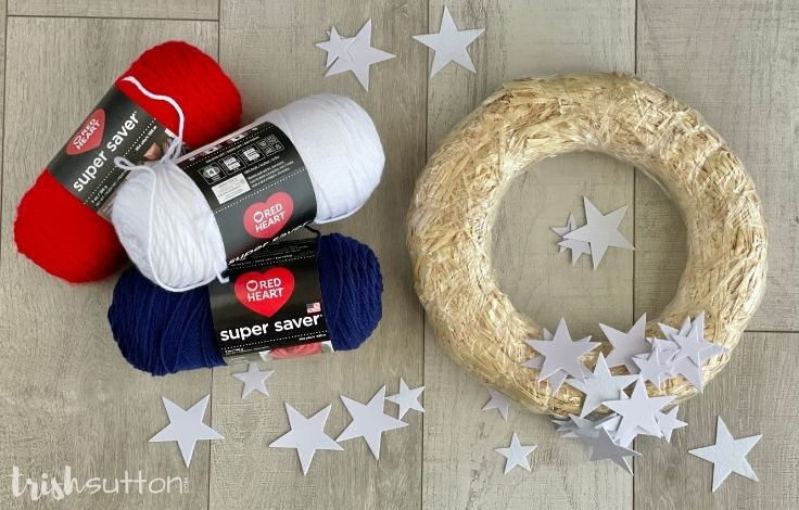 Red, white, and blue yarn beside felt stars and a straw wreath.