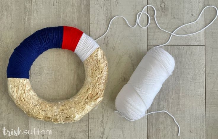 Spool of white yarn next to a wreath on a wood background.