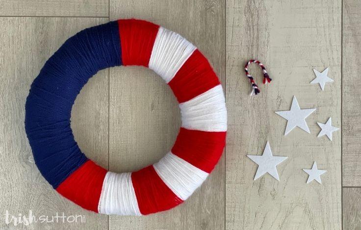 DIY yarn wreath next to white stars on a wood background.
