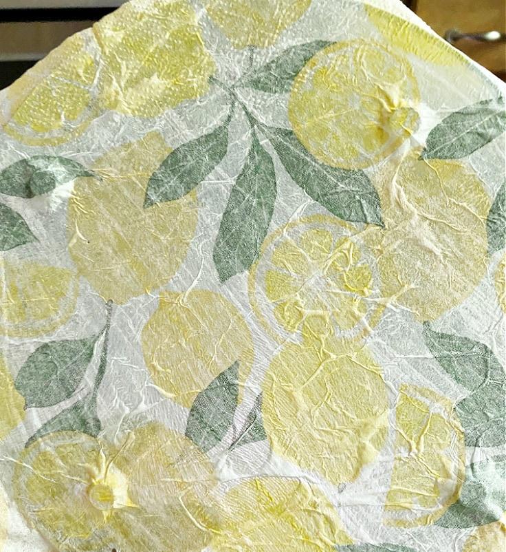 Mod Podge napkin on glass cutting board.