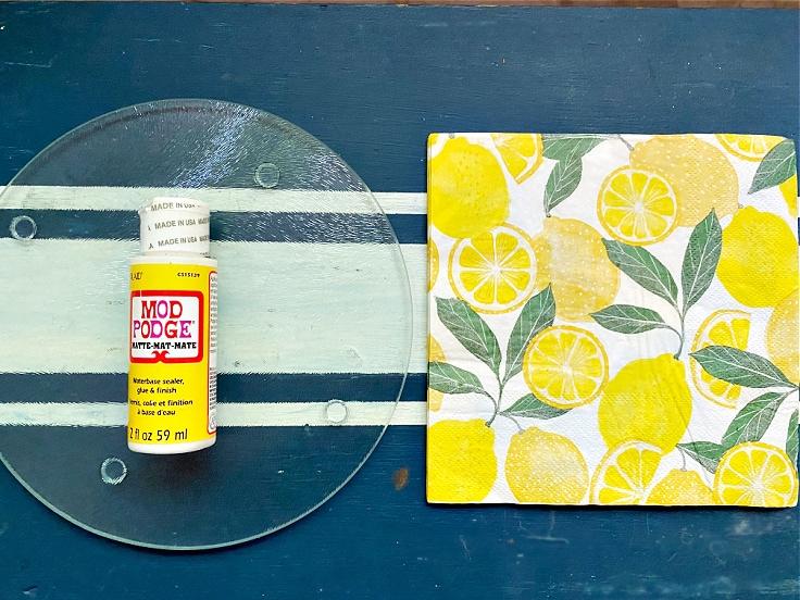 A glass cutting board, lemon print napkins, and a bottle of Mod Podge.