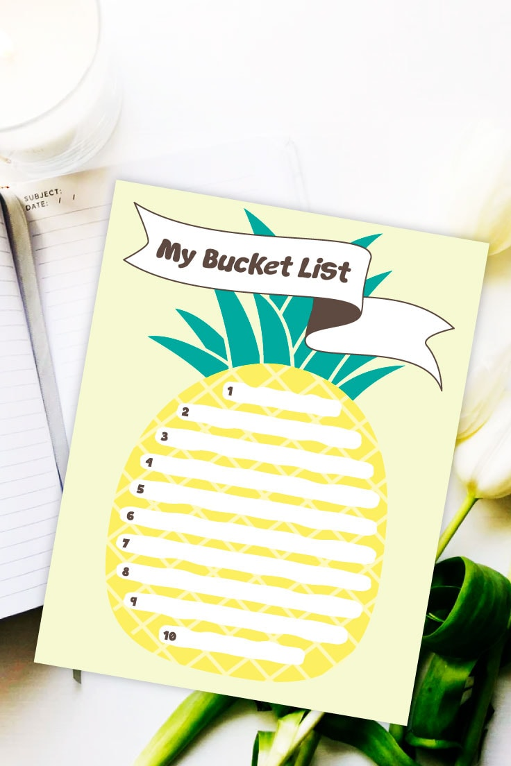 Preview of pineapple summer bucket list design on top of notebook and white flowers.